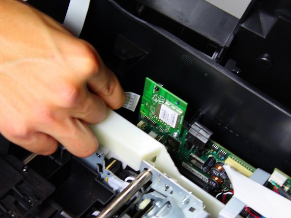 Remove the connector that binds the internal protective cover to the motherboard by pinching the blue part of the connector with two fingers and pulling it away from the motherboard.