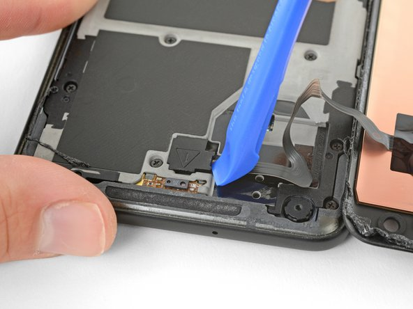 Use the corner of an opening tool to pry up the digitizer cable connector cover.