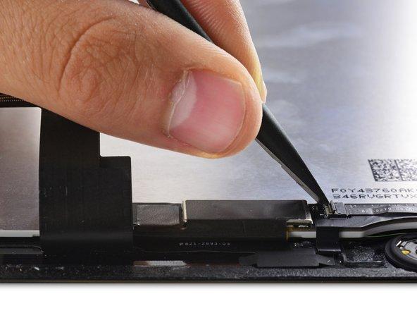 使用撬棒扁平的一端来翻转Home键线缆插座上的挡板。