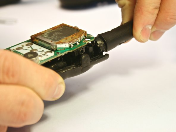 Image 2/3: To do this, grip the back faceplate in one hand and the antenna in the other. Pull and twist the antenna away from the back faceplate. The circuit board should be removed with the antenna, as they are attached.