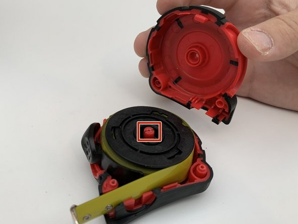 Pull the half shell off and remove the black spring housing from the plastic axle by pulling upward.
