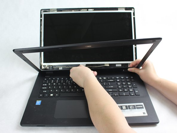 Using your fingers or a plastic opening tool, pry open the bezel that holds the screen in place.