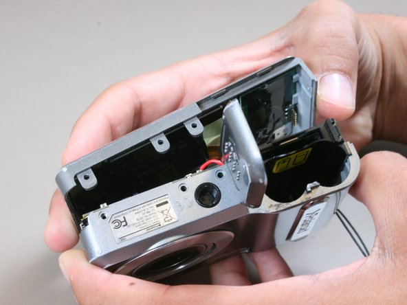Gently pull the half of the case with the screen (the back half) from the rest of the camera.