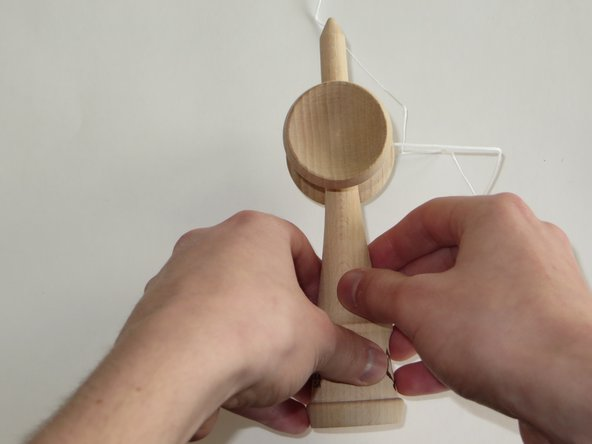 Flip the kendama over to the other side, so that the big cup is now on the left-hand side.