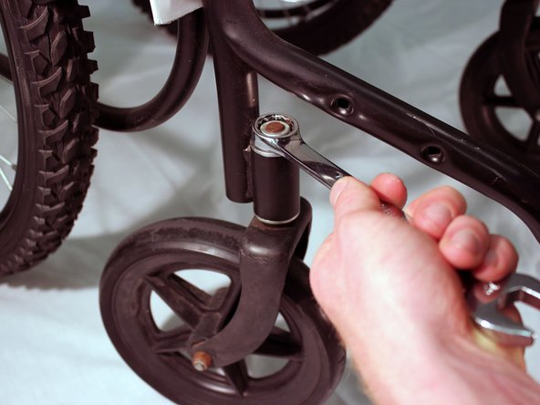 Use the socket head of the 19mm wrench to unscrew the nut that connects the castor wheel's fork to the steel frame