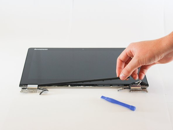 Remove the LCD  hinge cover by gently prying the pieces with a plastic spudger and lifting the hinge cover up and out.