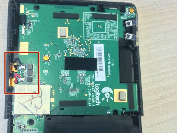 Image 1/3: Pull the gold buttons in towards the center of the device to detach logic board from case