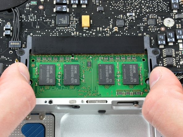 Release the tabs on each side of the chip by simultaneously pushing each tab away from the RAM.