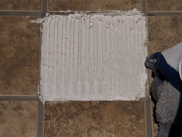 Quickly remove any adhesive from the surrounding tiles using a wet sponge or old rag, working quickly as the adhesive will begin to dry.