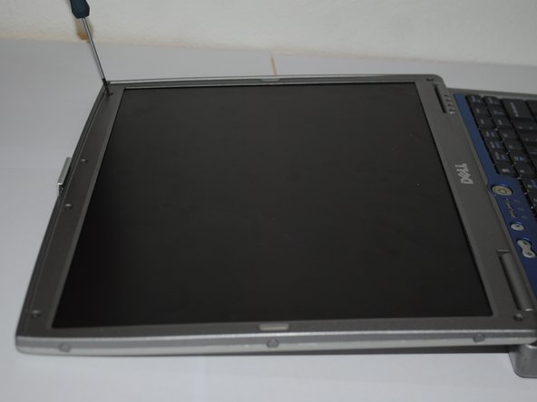 Use your fingernails or a flat-head screwdriver to remove the rubber dots around the screen by pushing any direction on them.