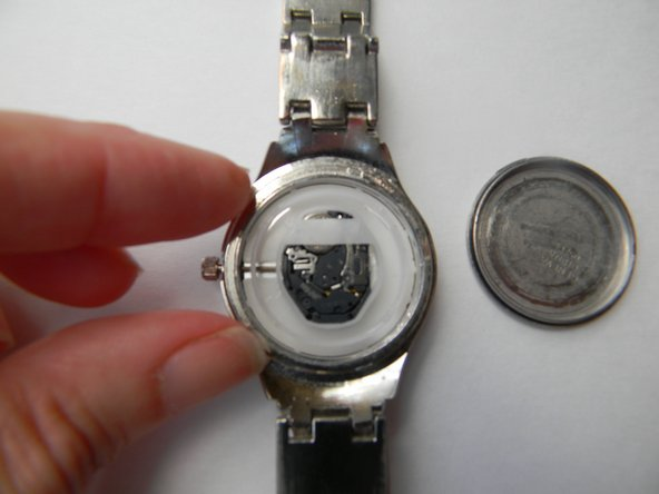 Use your fingers to insert the plastic white ring back into the watch.