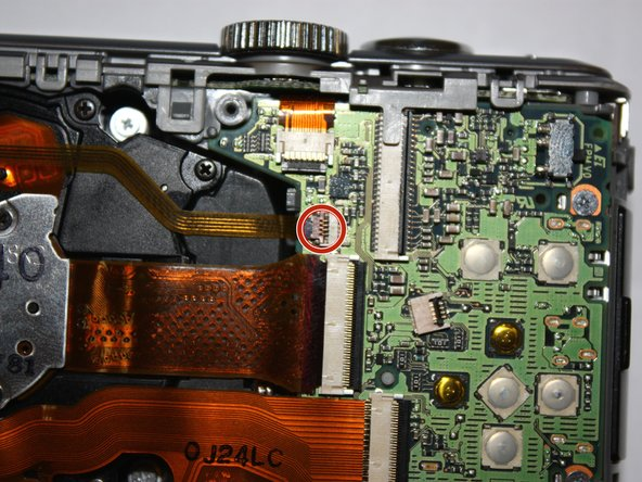 Use the 2.0 mm flathead to flip up the brown tab on the motherboard and carefully unseat the ribbon cable