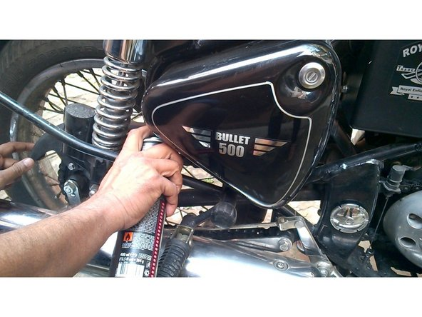 7.    Now spray the Motul Chain lube C-2 from a close distance while rotating the rear tyre slowly. 8.    Wait for 10 minutes. 9.    Put the Chain Cover in appropriate position and tight the screws.