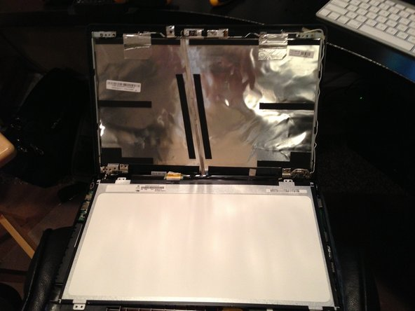 Gently remove the panel and set it face-down on the keyboard.  The cable plugs in at the base, and is secured with tape