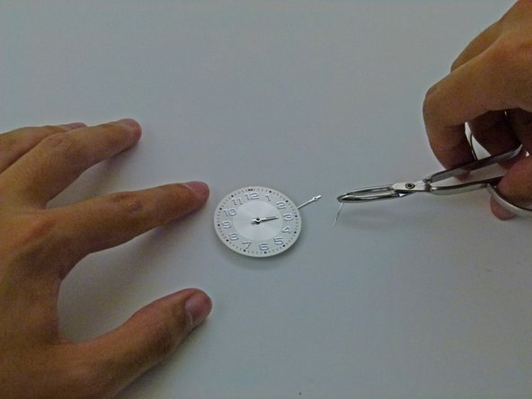 Press down on the hand, so that the hour hand is firmly attached to the center post.