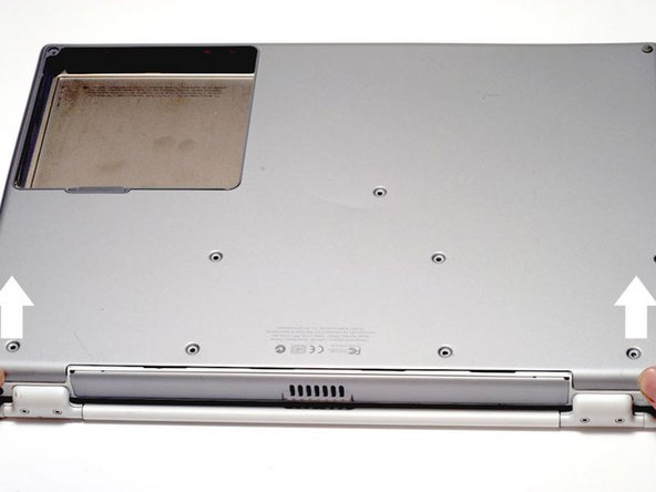 Image 1/1: The lower case may stick in the front on a tab just above the center of the DVD drive. Be careful as you work the case off, or you may break the thin strip of plastic just above the drive.