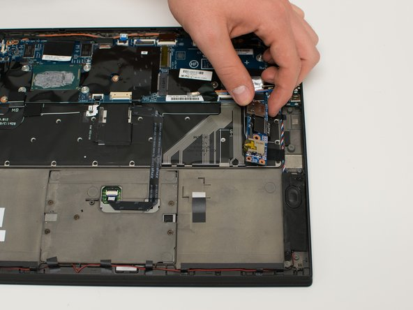 Pull the audio card straight back from the side of the laptop and flip it over, exposing the flat topped connector.