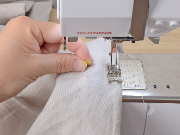 Be sure the needle penetrates the pant leg on only one side. It may be easier to position the pant leg around the arm of the sewing machine with the table removed. If you sew through both layers, you will sew the pant leg shut!