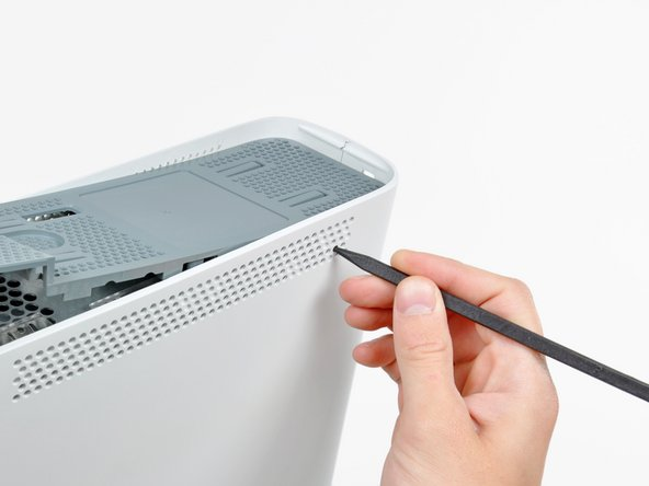 Use the tip of your spudger to release the clip on the top vent nearest the back of the  Xbox's upper case.