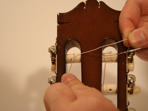Pull the end over the tuning peg to the right side.