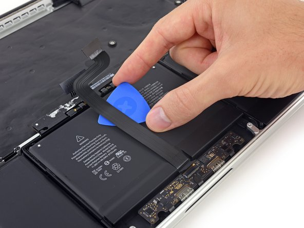 The ribbon cable is easily damaged. If necessary, use a little heat from an iOpener or hair dryer to soften the adhesive so you can remove it with less force.