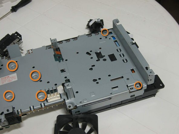 Image 2/3: And release the metal case from the DVD player, as indicated, using a small flat screwdriver