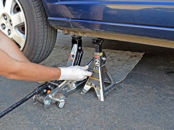 Lift up the lever on the jack stand to lower its saddle column, and remove the jack stand from under the car.