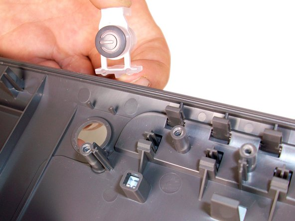 The power button is not clipped in and should easily slide off of the plate once the button circuit board is removed.