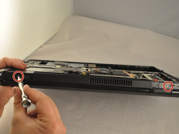 Using the PH1 screwdriver remove the two .75 mm screws from the hinge side of the laptop.