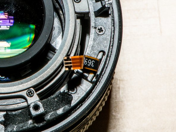 Drop on the zoom assembly. Carefully thread the focus encoder cable through the slot.