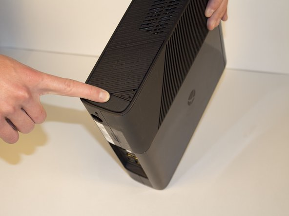 Orient your Xbox on the side where all the plugs are. Find the triangle-shaped release trigger.
