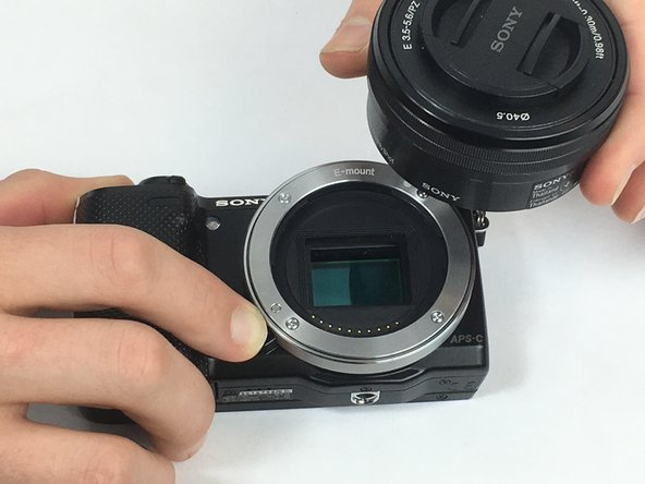 Image 3/3: With the hand holding the camera, simultaneously push down on the lens release button while twisting the lens counterclockwise then pull to remove the lens.