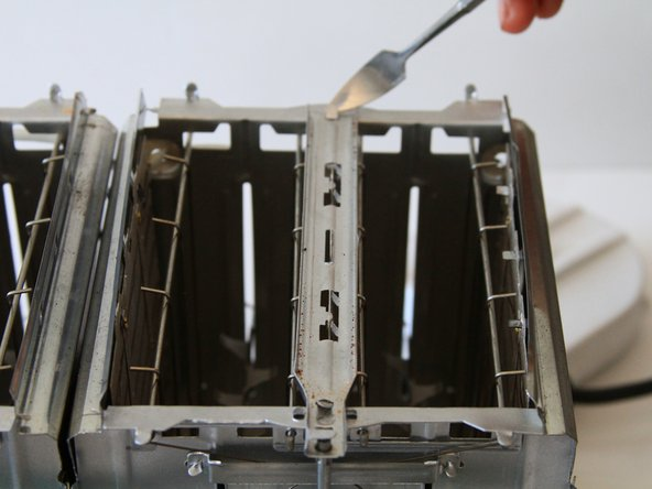 Image 1/3: Pull the metal spacer upwards to release from the toaster.