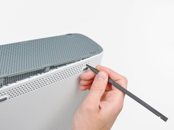 Use the tip of your spudger to release the clips on the bottom vent nearest the back of the Xbox.