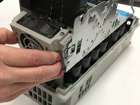 Remove the upper fan by pinching the tabs found on each side and pulling.