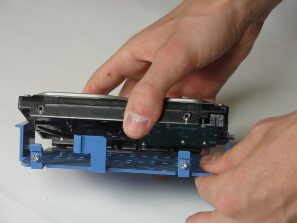 Pull the 2 blue tabs away from the hard drive and then pull the hard drive case down.