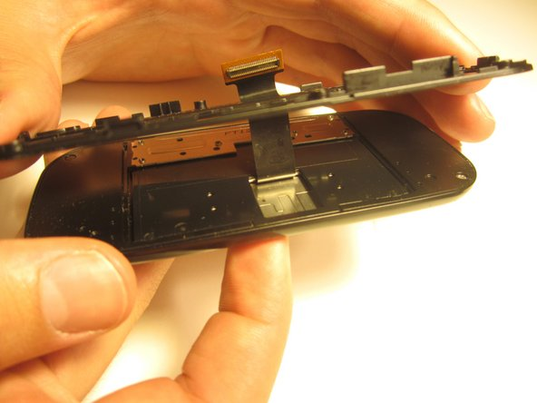 Pull the ribbon cable through the slit in the keyboard case to separate it from the sliding mechanism.
