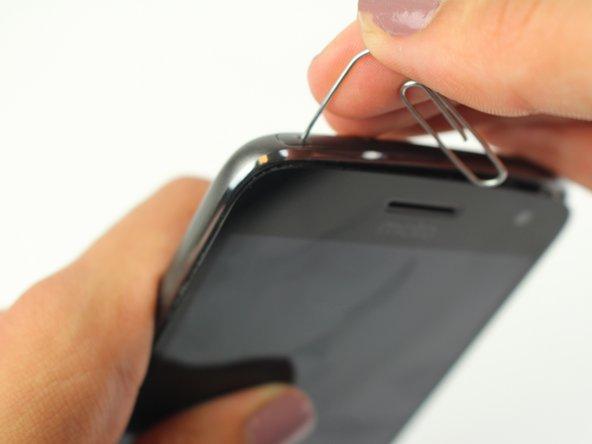 Entferne die SIM Karte. Schiebe dazu das Ende einer aufgebogenen Büroklammer in das kleine Loch in der oberen linken Ecke. Die SIM Karte wird herausspringen.