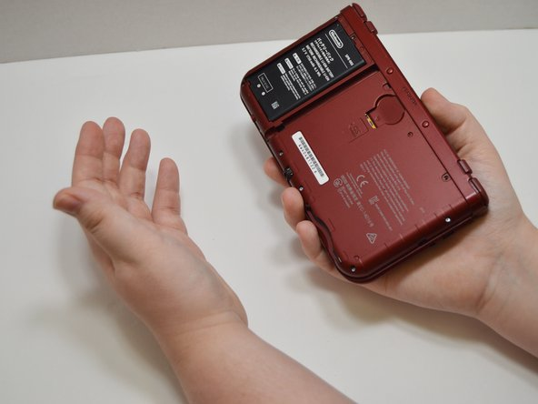 To remove the battery, hold the device with the battery facing up in one hand, with a finger securely gripping the lid of the device, and gently flip the device over to your other hand. The battery should fall into your hand.