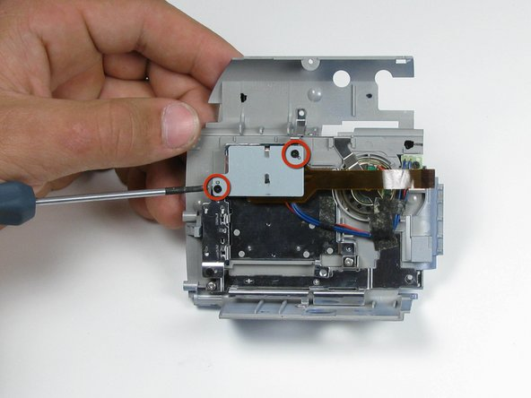 On the LCD housing plate, remove the two 4.5mm phillips screws on the ribbon cable plate using a #00 philips screwdriver.
