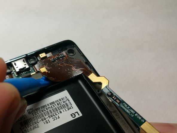 Use a small prying tool to detach the Micro-USB circuitry from the case of the phone