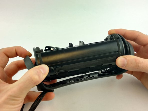 Use your hands to carefully remove the outer frame to expose the inner components of the speaker.