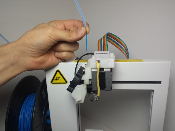 Disconnect the large colored ribbon cable on the top of the printer by wiggling slightly side to side and pulling up to disconnect.