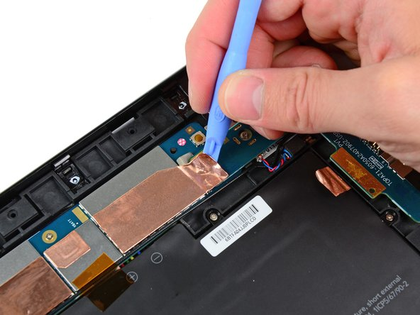 Use the edge of a plastic opening tool to peel up the two pieces of copper tape covering the USB connector board near the battery and the motherboard.