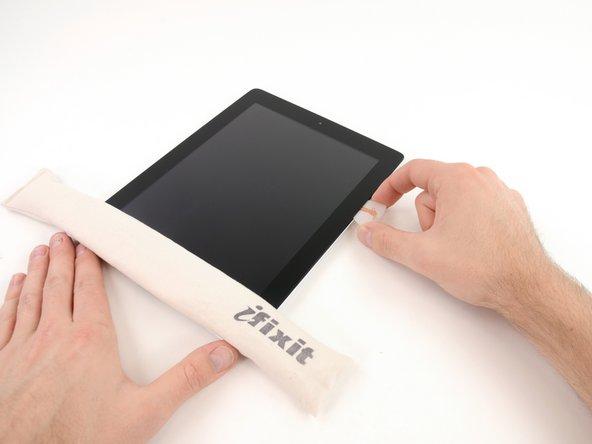 Während die Unterkante vom iOpener erhitzt wird, fange an, den Kleber an der rechten Kante des iPads zu lösen.