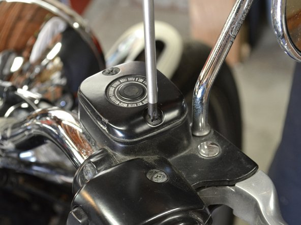 To prevent spilling any brake fluid, first clean the area around the master cylinder with a clean rag, then replace the cover.