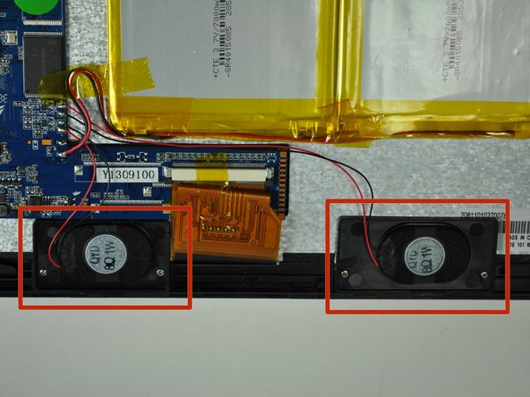 The speakers are located on the bottom of the device, below the battery and adjacent to the motherboard.