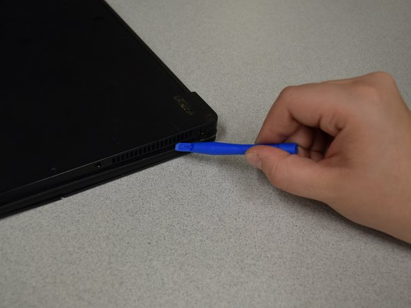 Use a spudger to carefully remove the back cover of the laptop.