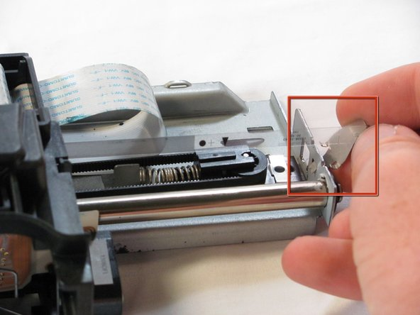 Image 1/2: Grasp the metal tab holding the encoding strip and pull it away from the track while pulling it up.