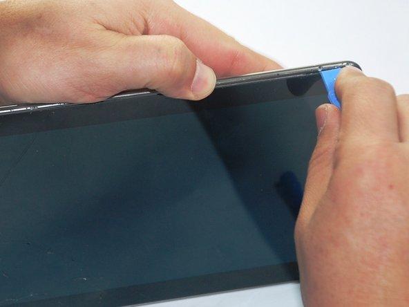 Insérez l'outil de levier entre l'écran en verre et la reliure d'argent. Faites pivoter l'écran jusqu'à ce que l'écran soit séparé de l'arrière de la tablette.